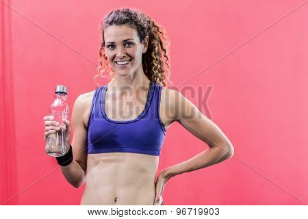 Portrait of a muscular woman holding a water bottle