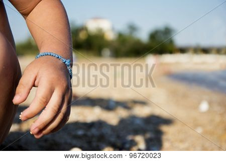 Kid's Arm With Bracelet On Sandy Beach