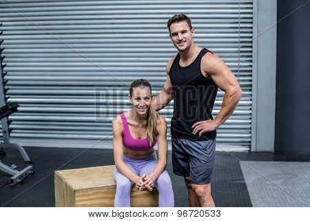 Portrait of a standing and sitting muscular couple