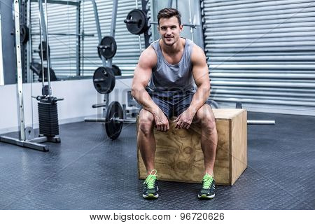 Portrait of a muscular man sitting on a wooden box