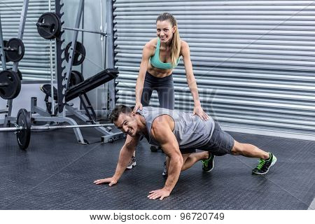 Portrait of a muscular man on a plank position with his coach