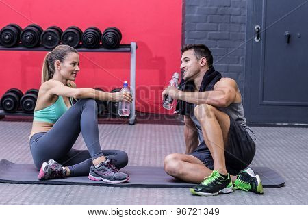 Sitting muscular couple talking together while drinking water