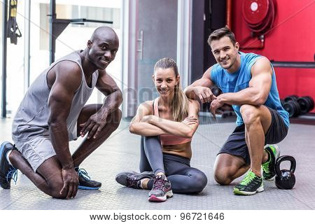 Portrait of three muscular athletes kneeling on the ground