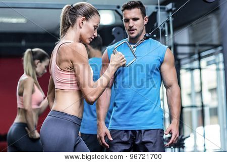 Trainer assisting a muscular woman doing pulling exercises