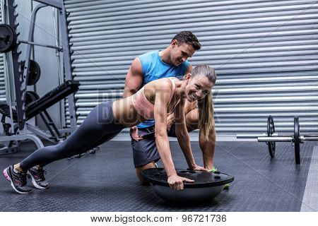 Trainer supervising a muscular woman doing bosu ball exercises