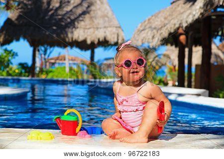 toddler girl playing in swimming pool at beach