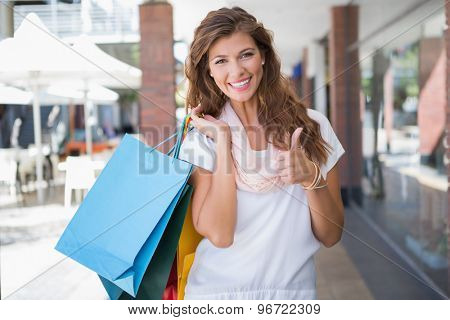 Portrait of smiling woman with shopping bags looking at camera and showing thumbs up at the shopping mall