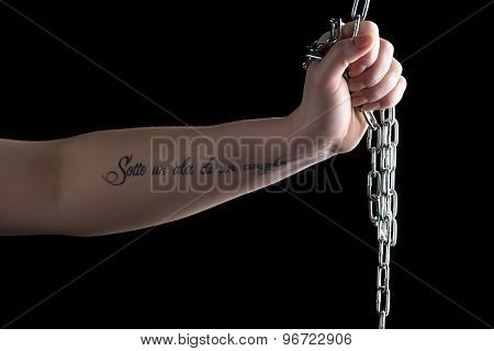 Photo of woman's hand with chain and tattoo, left