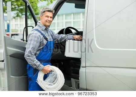 Worker With Toolbox And Cable Entering In Van