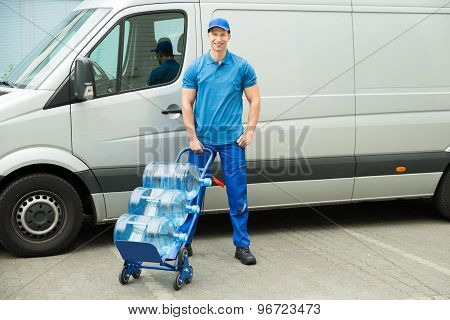 Delivery Man Holding Trolley With Water Bottles