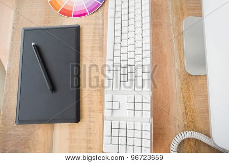 Upward view of table wood with graphic tablet and computer