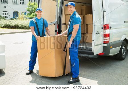 Two Movers Loading Boxes In Truck