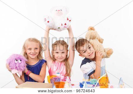 Smiling children holding soft toys