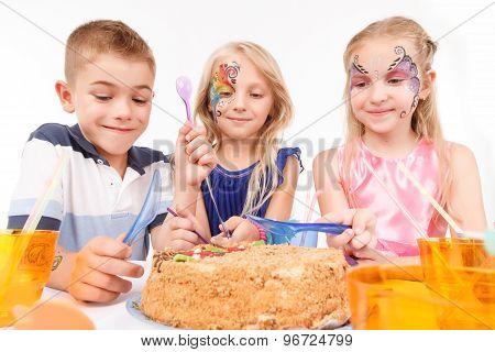 Joyful children eating birthday cake