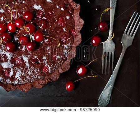 Chocolate Tart With Ganache And Cherry. Dark Style Photo.