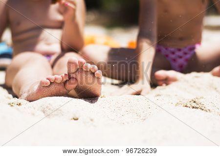 Children's Feet In Sand On The Beach