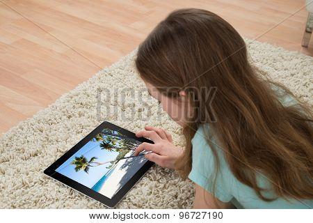 Girl On Carpet Looking At Digital Tablet