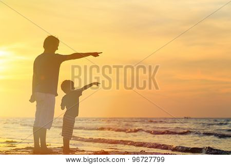 father and son at sunset beach