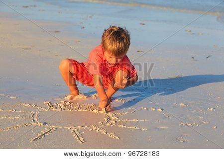 little boy drawing sun on sand beach