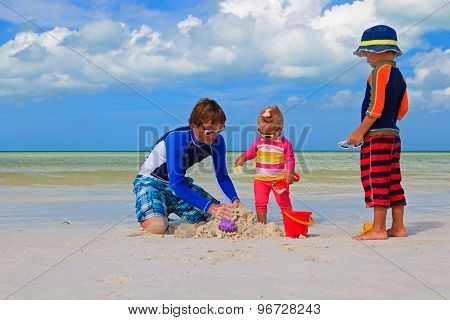 father and two kids playing with sand on the beach