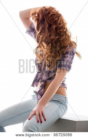 Curly red-haired girl in sexy casual clothing