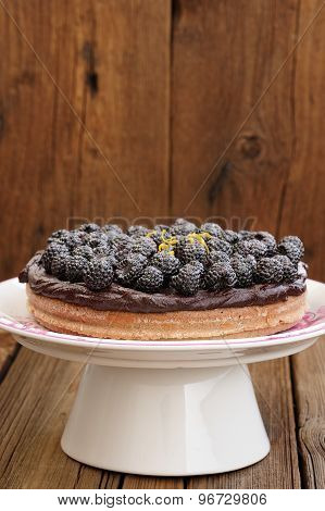 Tasty Homemade Chocolate Pie With Ganache, Decorated With Many Fresh Blackberries, Lemon Peel And Ic