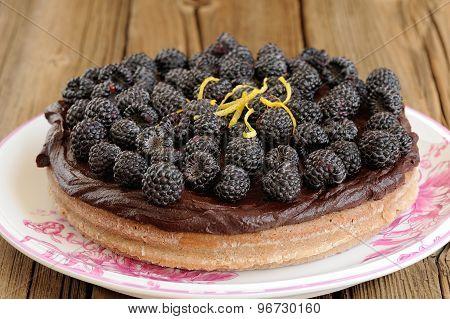 Tasty Round Homemade Chocolate Pie With Ganache, Decorated With Fresh Blackberries, Lemon Peel And I