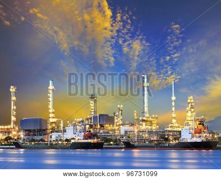 Tanker Ship And Petrochemical Oil Refinery Industry Plant With Beuatiful Lighting Against Dusky Sky