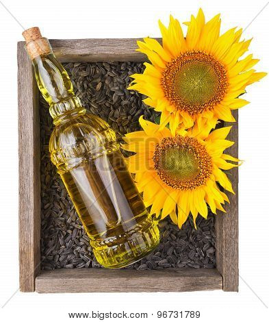 old rough wooden box with sunflowers, oil bottle and seeds