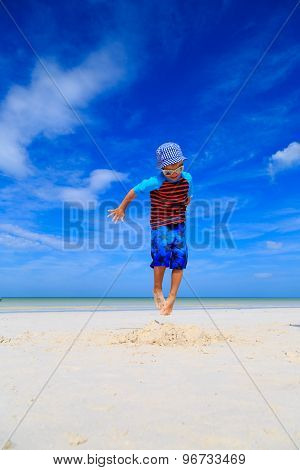 little boy jumping on the beach