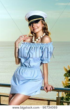 Attractive beautiful woman in captain hat near sea