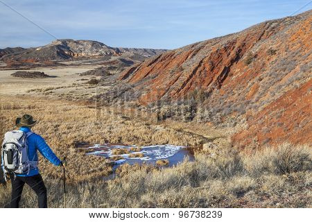 male hiker with a backpack in a rugged Colorado landscape - Red Mountain Open Space near Fort Collins, winter scenery