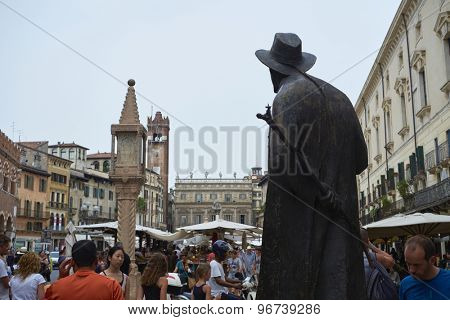 VERONA, ITALY - JULY 13: Bronze statue of poet Berto Barbarani overlooking Piazza delle Erbe. July 11, 2015 in Verona.