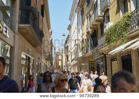 VERONA, ITALY - JULY 11: Busy Via Mazzini with Lamberti Tower in the far background. July 11, 2015 in Verona. Via Mazzini is one of the main commercial streets in Verona.
