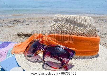 Straw Hat, Sunglasses And A Book On The Beach With Sea In Backgound
