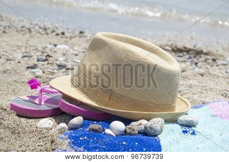 Straw Hat Slippers And A Towel On The Beach With Sea In Background