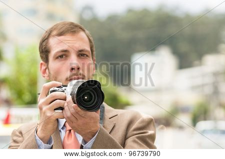 Successful attractive male photographer wearing brown suit working outdoors in traffic urban environ