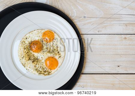 Plate with fried eggs on black tray, wooden table