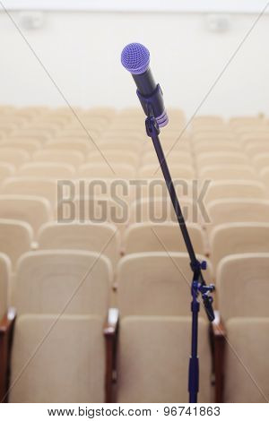 The image of microphone and blurred auditorium in the background
