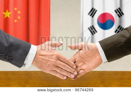 Representatives Of China And South Korea Shake Hands