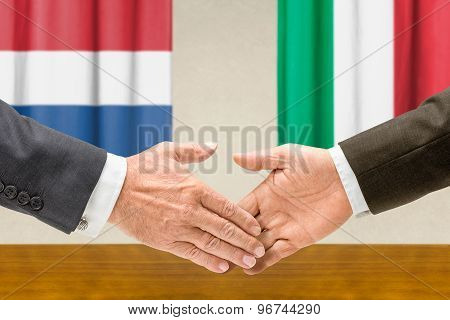 Representatives Of The Netherlands And Italy Shake Hands