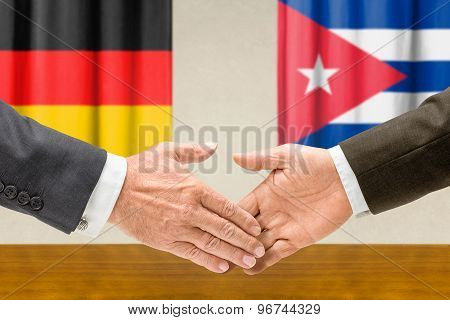 Representatives Of Germany And Cuba Shake Hands