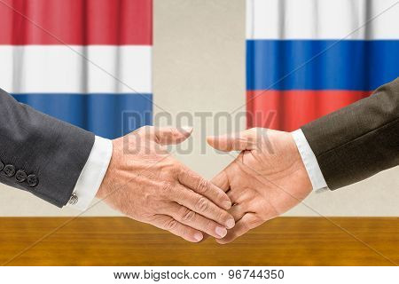 Representatives Of The Netherlands And Russia Shake Hands