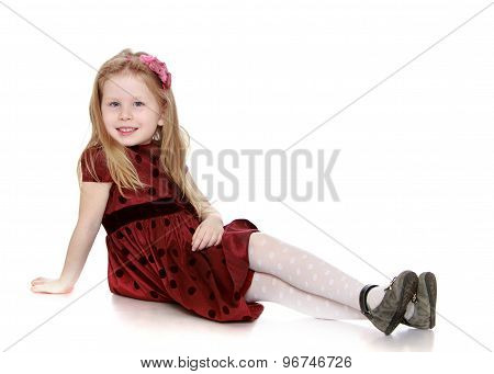 Adorable little girl sitting on the floor