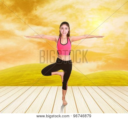Woman Doing Yoga Exercise On Wood Floor With Field At Sunset