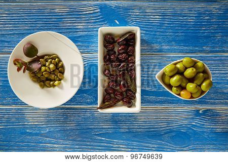 Mediterranean pickles tapas black olives and capers on blue wood table