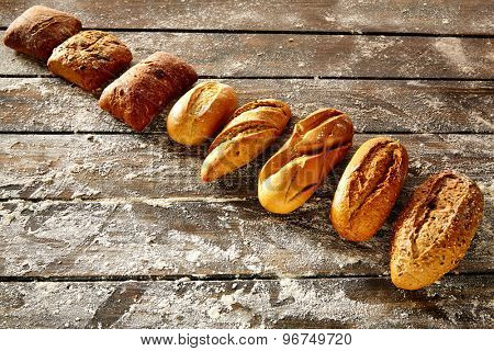 Breads varied in a row on rustic wood table with wheat flour
