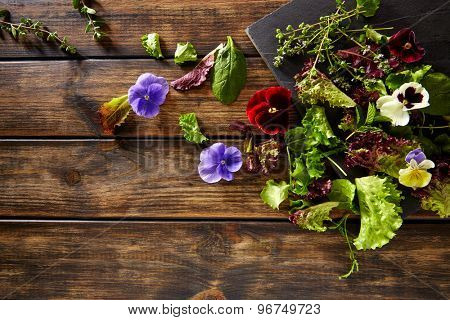 Fresh saland ingredients lettuce flowers spinach on rustic wood