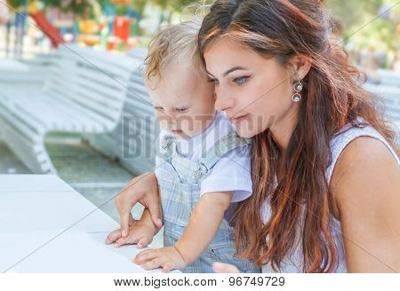 mother and child - baby boy - enjoying meal time in street cafe, restaurant, family time, lunch in outdoor restaurant