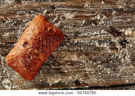 Bread loaf in a rustic wood and wheat flour aerial view